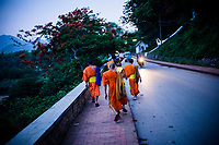 Monks walk the streets of Luang Prabang in Laos at dusk.