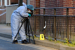 © Licensed to London News Pictures. 06/05/2018. LONDON, UK. A member of the forensics team at work near an evidence marker as police cordon off Palmerston Road in Wealdstone, near Harrow, north west London, following reports of two separate shooting incident around midday on Sunday 6 May 2018.  The two victims are a 12 year old boy and a15 year old boy.  Investigations are ongoing.  Photo credit: Stephen Chung/LNP