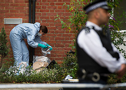 © Licensed to London News Pictures. 27/07/2015. London, UK. A forensics officer with evidence bags. Police and scene of crime officers at Collette House in Acton, West London, where the body of a woman in her 30s was found this morning (Mon). Police are currently searching for Michael Meanza  aged 47 in connection with the death.  Photo credit: Ben Cawthra/LNP