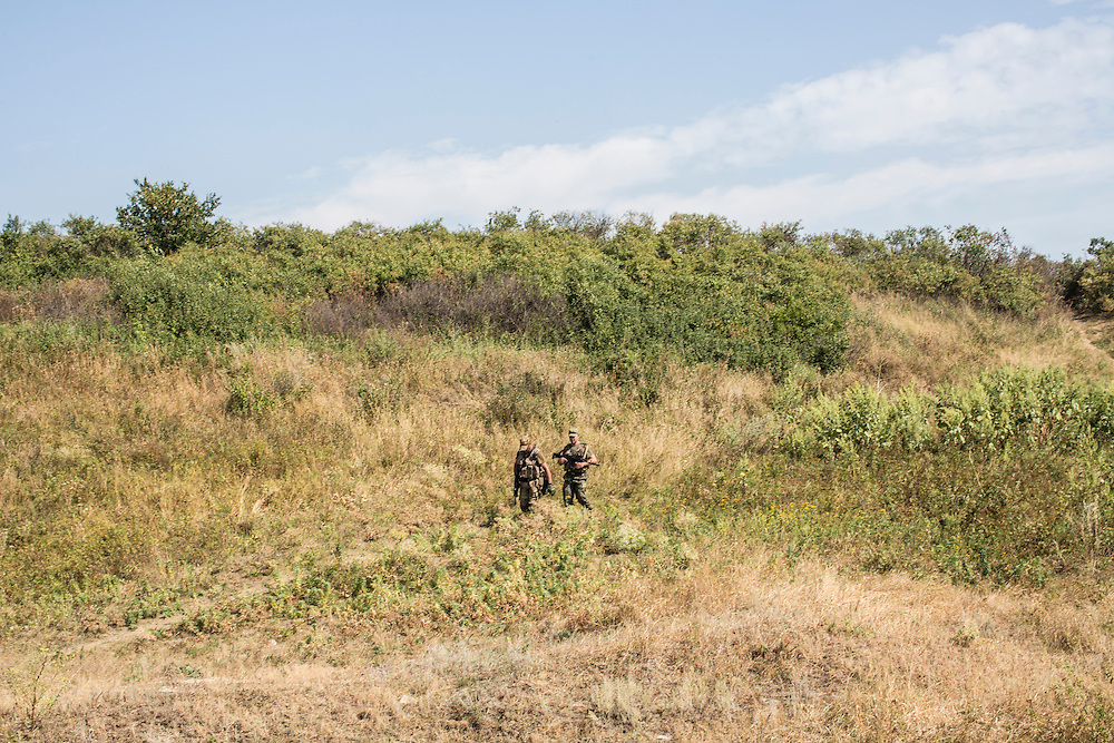 CHERMALYK, UKRAINE - AUGUST 29, 2015: Two Ukrainian soldiers walk in a field near the front line between Ukrainian territory and that controlled by pro-Russian rebels in Chermalyk, Ukraine. Two days earlier, a nearby farm was shelled by rebels based just across the nearby Kalmius River, with a level of skill that the soldiers felt indicated they were being targeted by professional Russian soldiers rather than rebel irregulars. CREDIT: Brendan Hoffman for The New York Times