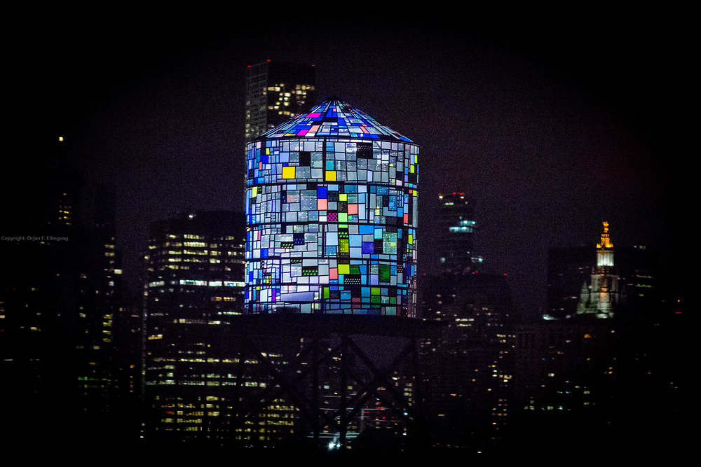 A stained glass watertower sits on the rooftop of a building in Brooklyn Bridge Park. The stained watertowers are made by the New York based artist Tom Fruin.