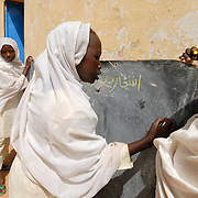 Sudan, Darfur. Displaced people. Dar El Salam School , Krindig Two camp. Two young girls write on a blackboard.