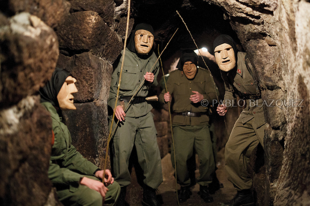 The Machurreros from Pedro Bernardo pose for pictures inside a cave before walking the streets during Carnival on February 6, 2016 in Pedro Bernardo, in Avila province, Spain. The origins of this pagan festival are unknown. The Machurreros wear wood masks, a military dress, black handkerchief, cowbells, and hold wicker stick. The festival disappeared after Dictator Franco forbid carnival festivals in 1937, but it was recently recovered. Before disappearing, male villagers after the military service, used to dress as Machurreros as they run along the streets scaring children and adults with their wicker stick to bring fertility to the land and expel the evil spirits. (© Pablo Blazquez)