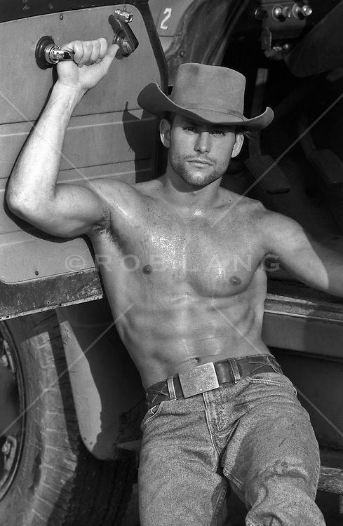 handsome cowboy outdoors without a shirt by a truck
