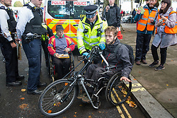 London, UK. 13 October, 2019. Police officers arrest disabled climate activists from Extinction Rebellion using Section 14 of the Public Order Act 1986 during a protest outside New Scotland Yard against tactics employed by police officers which impinge on the right to protest of disabled activists, including the confiscation of wheelchairs, wheelchair ramps, accessible toilets and tents.