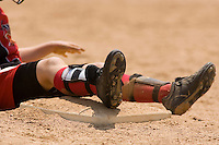 Baseball players feet and legs after sliding onto a base.