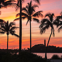 South Florida lighthouse photography from photographer Juergen Roth showing beautiful sunset light framing the Jupiter Inlet Lighthouse. The famous red lighthouse is located in Jupiter, FL in Palm Beach County. The photography image was captured from DuBois Park that stretches along the Jupiter Inlet and Atlantic Ocean.<br />