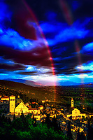 """""""Rainbow of God divides the sky between San Rufino and St. Clare of Assisi""""...<br /> <br /> This image is perhaps the most blessed and miraculous of my Italian journey.  Upon arrival early that day in Assisi, I began taking photos the second I parked at Hotel Giotto just inside the walls in the foothills of Assisi. Perhaps Saint Francis arranged the dramatically perfect skies and coordinated every encounter. Beginning at the Basilica of Saint Francis, every second of the climb to the top of the mountain to the fortress Rocca Maggiore, a new surprise awaited around every corner.  Upon my final steps to the top at almost sunset, the clouds parted and the low sun brightened as a slight mist of rain came down.  Looking back over my shoulder, I was mesmerized at the appearance of a double rainbow from the heavens shining down between the Duomo of Saint Rufino, and the Basilica of Saint Clare. I was able to take a few horizontal and vertical images of the great length and depth of the rainbow just before the sun dropped down below the horizon...and, it slowly faded.  My Italian journey was now and forever blessed by the hand of God."""