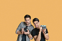 Portrait of young male friends with digital camera over colored background