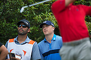 Jordan Spieth and his caddy, Michael Greller, look on as Justin Thomas tees off during the first round of the AT&T Byron Nelson in Las Colinas, Texas on May 28, 2015. (Cooper Neill for The New York Times)