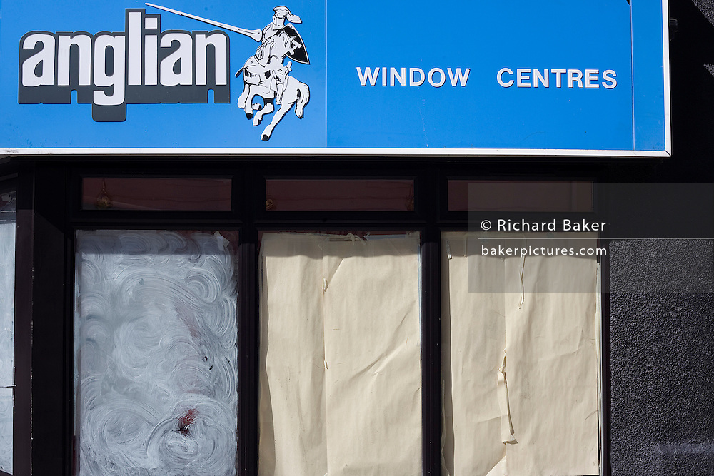 White emulsion paint has been smeared and paper sheets placed over an Anglian window centre front window in Weston-super-Mare, a victim of the UK recession.
