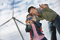 Girl (5-6) using binoculars with father at wind farm
