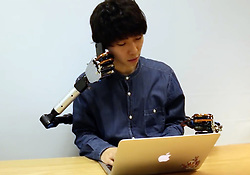 May 30, 2017 - Tokyo, Japon - Humans of the future could be multi-tasking – using an extra pair of arms and hands.Researchers are developing the additional set of limbs which are controlled by movements in the feet and knees.MetaLimbs, or Multiple Arts Interaction Metamorphism, is a set of robotic arms fixed to a user's back,They reach around under their human arms and are controlled by sensors attached to the legs.Positional tracking balls on the knees and feet direct the arm movement.A sock device allows the movement of your toes to control the grasp of the robot hands.Haptic sensors on the robot hands generate force feedback to the feet. The arms are intended to be worn while sitting, but can be used while standing depending on the task . The team behind it are from the Inami Laboratory at the University of Tokyo in Japan.Uses could include complex and delicate tasks.One example shown is holding a circuit boards with two hands while a robot arm does some soldering.The team is presenting the device in Los Angeles at the SIGGRAPH2017 Conference on Computer Graphics and Interactive Techniques in July. # DEUXIEME PAIRE DE MAINS (Credit Image: © Visual via ZUMA Press)