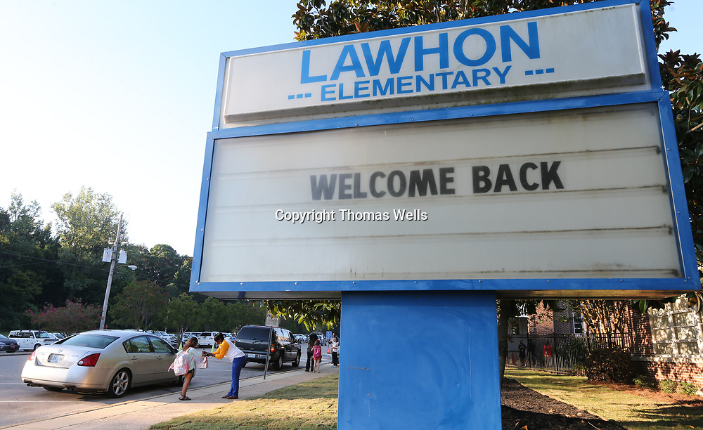 "Students make their way past the ""welcome back"" sign and to their classroom for their first day of school."