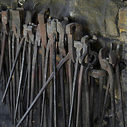 Pliers and pincers in the Forge, at the Chateau de Guedelon, a castle built since 1997 using only medieval materials and processes, photographed in 2017, in Treigny, Yonne, Burgundy, France. In the forge, the site's blacksmiths repair and manufacture all the metalwork needed for the project, including chisels, axes, adzes, gates and hinges. The Guedelon project was begun in 1997 by Michel Guyot, owner of the nearby Chateau de Saint-Fargeau, with architect Jacques Moulin. It is an educational and scientific project with the aim of understanding medieval building techniques and the chateau should be completed in the 2020s. Picture by Manuel Cohen