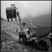 Gemeinwerk auf der Alp: Nach dem Winter und Regenfällen müssen die Wege wieder instand gestellt werden. Was früher harte Hände-arbeit war, wird heute wo möglich mit Maschinen erledigt - dennoch kein Kinderspiel. Alpbetrieb in der Nähe vom Klausenpass. © Romano P. Riedo