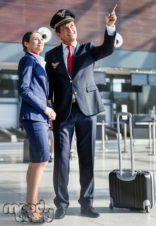 Pilot pointing aircraft while talking to flight attendant in airport