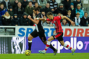 Andy Carroll (#7) of Newcastle United dribbles the ball forward, pursued by Jan Bednarek (#35) of Southampton during the Premier League match between Newcastle United and Southampton at St. James's Park, Newcastle, England on 8 December 2019.
