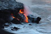 A small portion of the lava bench breaks away, relieving pressure from within, allowing molten lava to flow forth and into the sea at the Waikupanaha ocean entry.