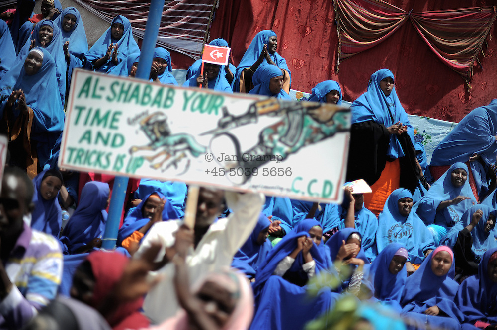 Street images from the destroyed city of Mogadishu... woman at a rally selebrating the mayor of the city.Death or Play. Women&acute;s Basketball in Mogadishu<br /> Women's basketball? In Europa and the U.S., we take it for granted. But consider this: In Mogadishu, war-torn capital of Somalia, young women risk their lives every time they show up to play.<br /> Suweys, the captain of the Somali women&acute;s basketball team, and her friends play the sport of the deadly enemy, called America. This is why they are on the hit list of the killer commandos of Al Shabaab, a militant islamist group, that has recently formed an alliance with the terrorist group Al Qaeda and control large swathes of Somalia.<br /> <br /> Al Shabaab, who sets bombs under market stands, blows up cinemas, and stones women, has declared the female basketball players &bdquo;un-islamic&ldquo;. One of the proposed punishments is to saw off their right hands and left feet. Or simply: shoot them.<br /> <br /> Suweys&acute; team trains behind bullet-ridden walls, in the ruins of the failed city of Mogadishu &ndash; protected by heavily armed gun-men. The women live in constant fear of the islamist killer commandos. Stop playing basketball? Never, they say.<br /> Women&acute;s basketball in the world&acute;s most dangerous capital. Female basketball in Mogadishu, Somalia.<br />