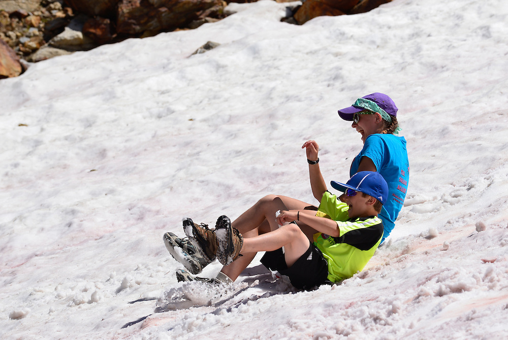 Kids glissading down a snowfield high in the Wallowa Mountains of Oregon.