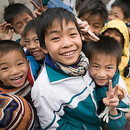 Color film photograph of a group of children posing and laughing in front of the camera after school in Dai Bai bronze casting craft village, Bac Ninh Province, Hanoi outskirts, Vietnam, Southeast Asia