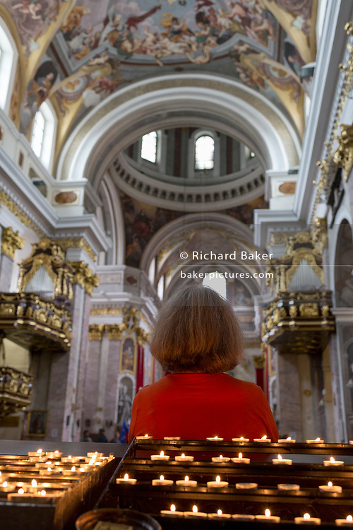 A lady visitor to the Cathedral of saint Nicholas sits in a pew with her back to lit candles, in the Slovenian capital, Ljubljana, on 28th June 2018, in Ljubljana, Slovenia.