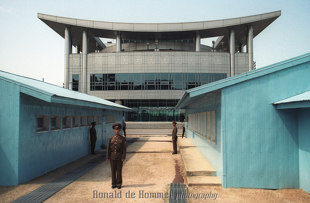 Panmunjom,North Korea july 2001. the famous closed border between North and South Korea. A North Korean Guard looks at the fancy modern South Korean ternminal where tourists are observing the North