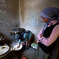 Aicha's is looking at her mother baking bread. She is saying that herself she has never prepare the dough or bake the bread. She is not interested to learn.