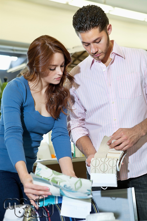 Young couple looking at textile samples in store