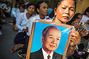 """04 FEBRUARY 2013 - PHNOM PENH, CAMBODIA: Cambodians sit near the National Museum with photos of former Cambodian King Norodom Sihanouk during his cremation service in Phnom Penh. Norodom Sihanouk (31 October 1922- 15 October 2012) was the King of Cambodia from 1941 to 1955 and again from 1993 to 2004. He was the effective ruler of Cambodia from 1953 to 1970. After his second abdication in 2004, he was given the honorific of """"The King-Father of Cambodia."""" Sihanouk died in Beijing, China, where he was receiving medical care, on Oct. 15, 2012.    PHOTO BY JACK KURTZ"""