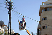 An electrician on an elevated platform reaching up to fix the electricity
