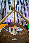 A giant saw blade is used as a gong in an installation exploring noise - The Turbine Festival 2015 - One City One Day - sponsored by Hyundai. The festival includes many activities for all ages exploring art and technology. The hall is decorated with giant white streamers.