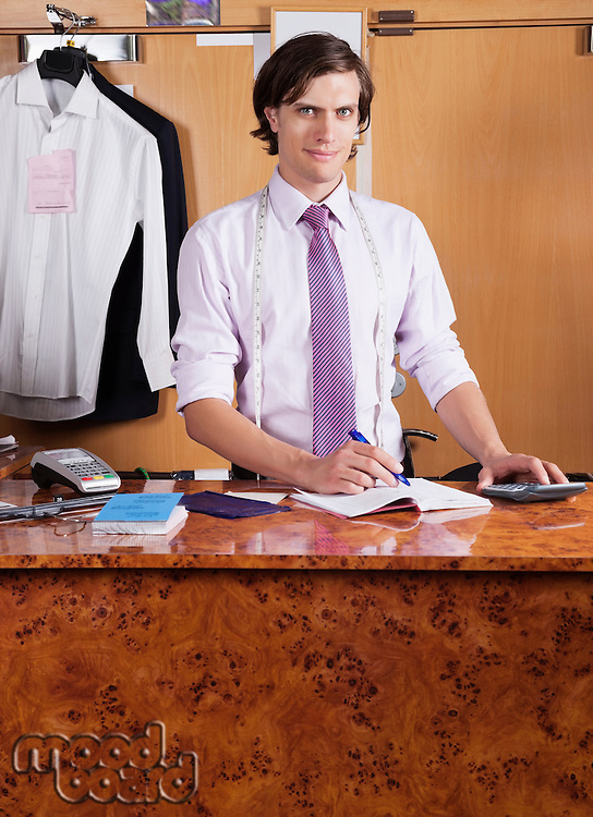 Portrait of confident owner making bills at counter