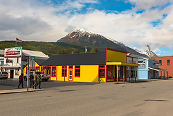 Alaska, USA -- April 29, 2016. Tourists walk down the street in Skagway, Alaska doing some sightseeing. Snow capped mountain in the background. Editorial Use Only.