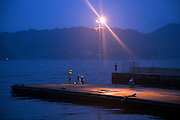 people recreational fishing at dusk