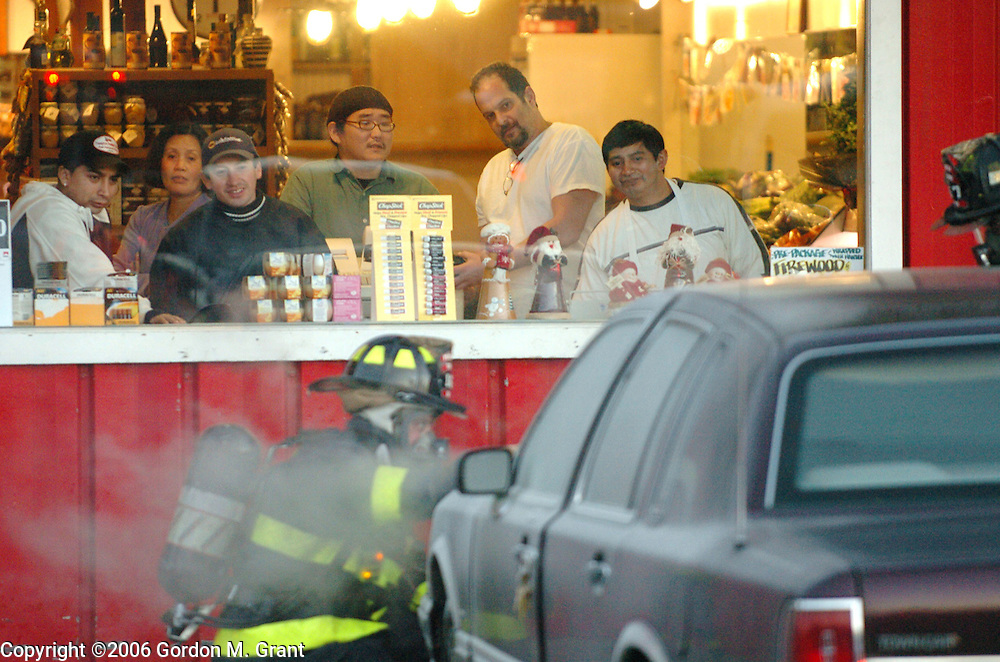 East Hampton, NY - 1/24/06 - Employees and customers of Hampton Country Market on Race Lane in East Hampton, NY watch as East Hampton Fire Dept. members put out a car fire in the parking lot late afternoon Friday January 24, 2006.     (Photo by Gordon M. Grant)