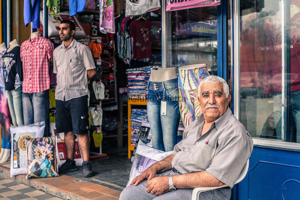 Chui, Rio Grande do Sul, Brazil. Mr. Shafik Ibrahim Khaled and his son Muats Khlid in front of their shop in Chui, on the Brazilian side of the border. Mr. Shafik, retail merchant, was one of the first Palestinan immigrants arrived here in 1959. Since then, He brought here in Chui more than 200 people among relatives and friends from the Palestinian territories. His son, Muats, was born in Jerusalem but has brazilian nationality  and has lived here for the past 25 years, all his life.