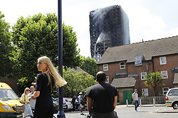 © Licensed to London News Pictures. 14/06/2017. London, UK. Members of public watching the Grenfell Tower fire as it's still  not under control 14 hours after the fire broke in west London on 14 June 2017. Photo credit: Tolga Akmen/LNP
