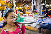 19 OCTOBER 2012 - BANGKOK, THAILAND:   A food stall worker delivers food and drinks the Bangkok Flower Market. The Bangkok Flower Market (Pak Klong Talad) is the biggest wholesale and retail fresh flower market in Bangkok.  The market is busiest between 3:30AM and 6AM. Thais grow and use a lot of flowers. Some, like marigolds and lotus, are used for religious purposes. Others are purely ornamental.         PHOTO BY JACK KURTZ
