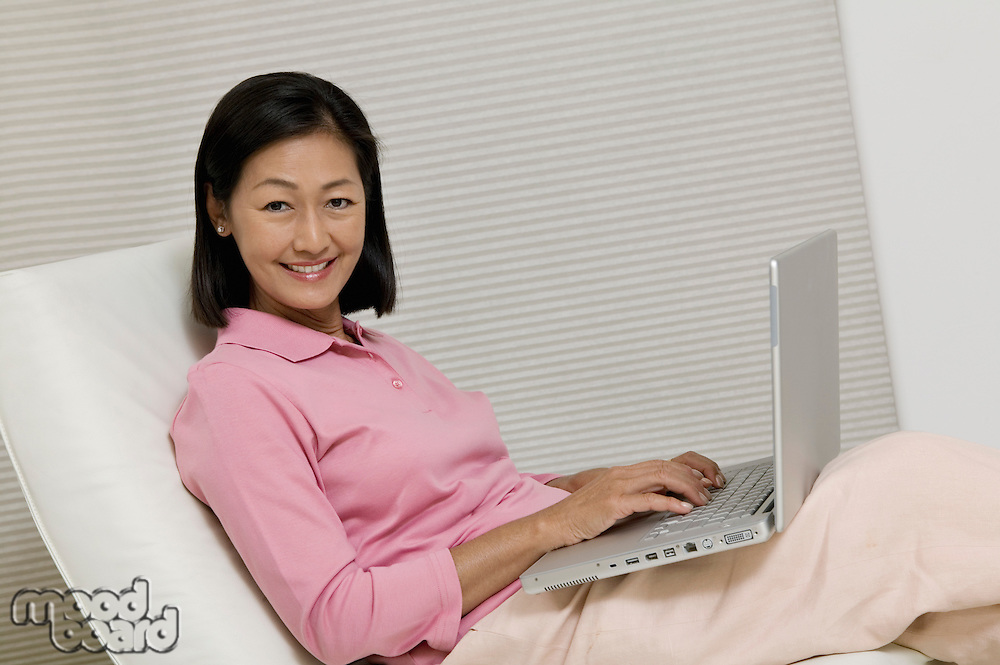 Woman in Chair Using Laptop