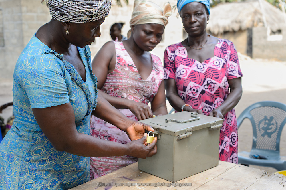 Members secure their savings at a 'Banking on Change' Village Savings and Loan Association (VSLA) meeting at Dabala Junction in the Volta Region of Ghana on 12 September 2012. Their cash box has three locks, with the key for each held by a different member; the box itself is held by a fourrth member. Association members contribute savings weekly and receive a payout commensurate with their inputs at the end of each year. Members may also access small loans, which many use to support entrepreneurial activities, and they make small insurance contributions which may be drawn upon in the event that an individual member has a financial emergency.