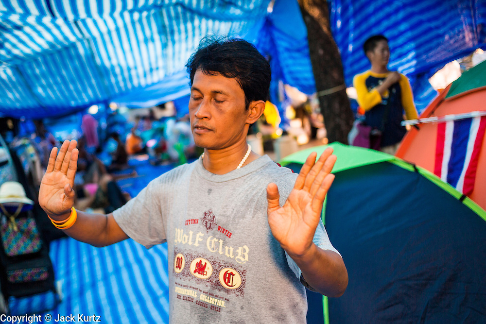 11 MAY 2013 - BANGKOK, THAILAND:  Yellow Shirt protesters dance to Thai country music in their encampment on Sanam Luang. A faction of the Yellow Shirts are camping at Sanam Luang, the royal parade ground in front of the Grand Palace, to show support for the Thai monarchy and the Thai Constitutional Court. The court has become a flash point in Thai politics because Red Shirts claim the court is biased against them and have been protesting against the court, calling for the justices' ouster and replacement with justices more open to the Red Shirts. The Yellow Shirt protest at Sanam Luang is calling for the Justices to remain on the court.    PHOTO BY JACK KURTZ