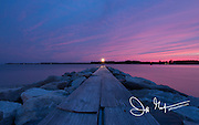 A dramatic pink and purple sky at sunset over a wood and stone jetty in Oxford, MD.