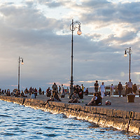 Tourists and locals enjoy the sunset on the Molo Audace in Trieste, Italy