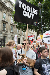 © Licensed to London News Pictures. 01/07/2017. London, UK. A protestors carries his dog on the People's Assembly anti-austerity demonstration as it passes Downing Street. Speakers include Labour Party Leader Jeremy Corbyn. Photo credit: Peter Macdiarmid/LNP