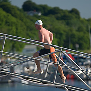 A male triathlete in a white swim cap and Oregon State shorts sprints up the gang plank toward the transition area.  Waterfront park, Bath, Maine.  2007 Shipbuilders Triathlon.