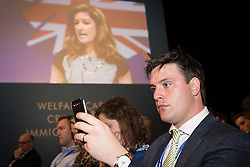 © Licensed to London News Pictures . 30/09/2013 . Manchester , UK . A delegate in the audience uses a mobile phone camera as Karren Brady , vice-chairman of West Ham United , addresses the conference ahead of the Chancellor's speech , this afternoon (Monday 30th September 2013) . Day 2 of the Conservative Party Conference 2013 at Manchester Central . Photo credit : Joel Goodman/LNP