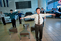 ©Tom Wagner 2004<br /> Mitsubishi Corp. showroom staff workout before the shop opens; Japan.<br /> Japan. Industry. Auto.