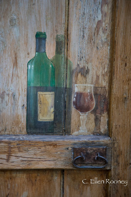 A wine bottle and glass painted on an old wooden door in Bagno Vignoni, Tuscany, Italy